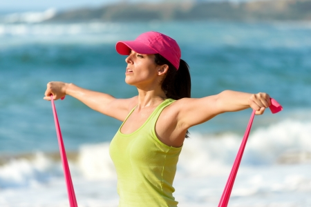 elastic band: Woman exercising and training shoulders with resistance band on summer Stock Photo