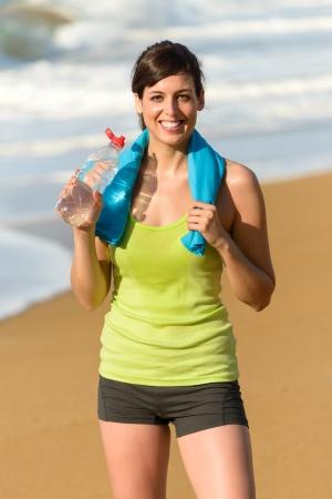 Gimnasio hermosa mujer de agua potable feliz y sudoración después de hacer ejercicio en el caluroso día de verano en la playa de Foto de archivo