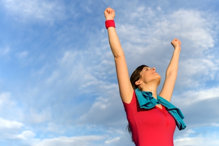 Happy successful fitness woman raising arms and winning after exercising