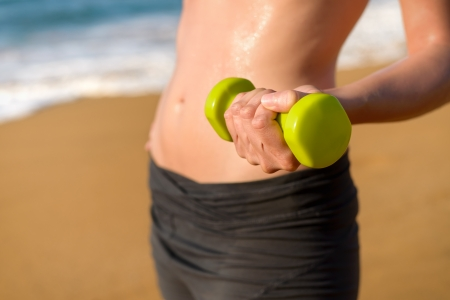 Sexy woman working out with dumbbell on beach in summer photo
