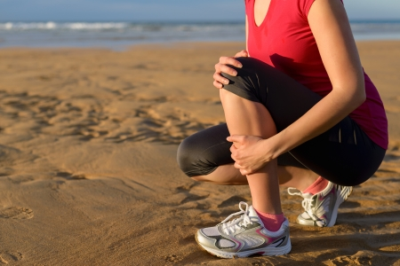 shin bone: Female runner clutching her shin because of a running injury and inflammation  Tibial periostitis hurt while jogging on beach  Stock Photo