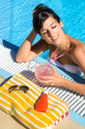 Happy woman relaxing in swimming pool  Beautiful girl on summer resort holidays drinking cocktail  photo
