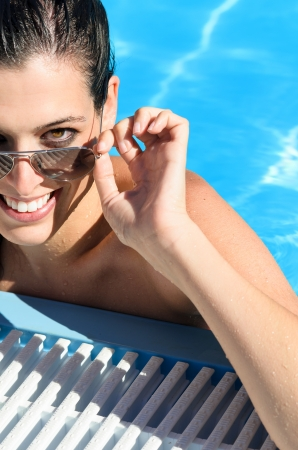 Beautiful and sexy woman face looking over her sunglasses in a pool in summer holidays  Brunette girl relaxing on hot sunny day  photo