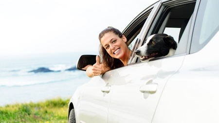 travelling: Happy woman on road trip with her pet out of the auto window towards coast landscape background. Stock Photo