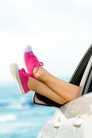 Car road trip vacation concept. Woman legs out the windows on sea background. Female legs out of window for freedom, travel and relax concept. Copy space photo