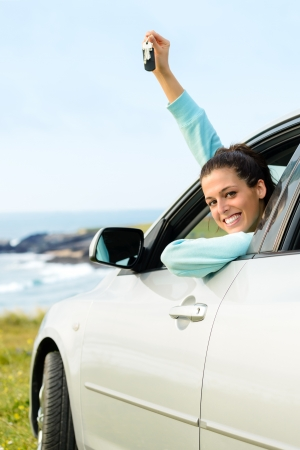 new car: Woman driving car and holding keys on summer travel
