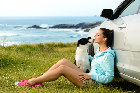 trip: Happy woman and dog sitting outside car on summer travel vacation