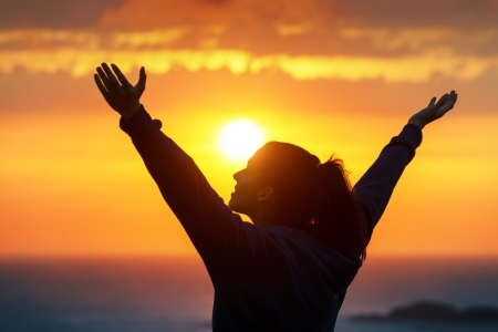 happiness people silhouette on the sunset: Free woman raising arms to golden sunset summer sky Stock Photo