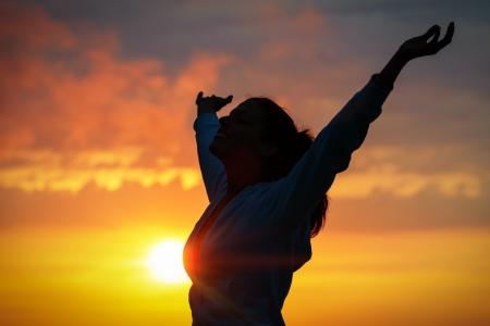 無料女性黄金の夕日に腕を上げる 写真素材