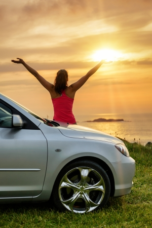 Free woman on car travel looking summer sunset and ocean  Female driver leaning on car bonnet raising arms to glow dusk sun  Traveling and freedom concept  Copy space  photo