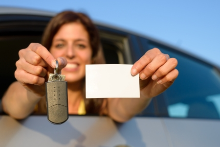 Happy teen girl showing new car keys and driving license  photo