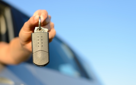 Female hand holding new car keys for rental, buying and travel concept  Copy space blue sky  photo