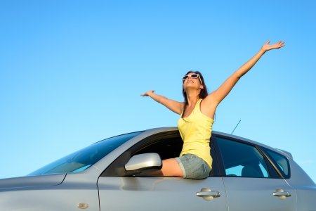 Joyful woman sitting on window new car raising arms up to the sky on summer trip  Blissful and fun happy girl on travel vacation