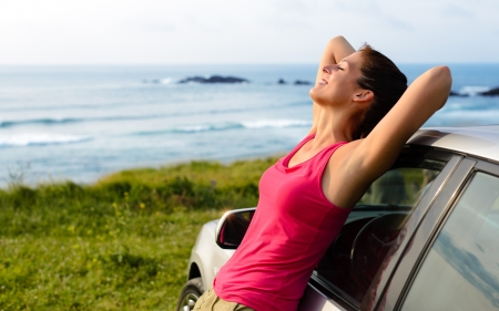 peacefulness: Woman leaning on car on summer travel to coast  Happy girl on road trip enjoying peace and silence relaxing on nature  Stock Photo
