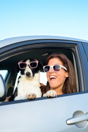 Woman and dog driving car on summer travel and having fun  Speed and vacation with pet funny concept  photo