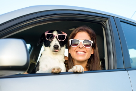 Vrouw en hond in de auto op zomer reizen Grappige hond met een zonnebril reizen Vakantie met huisdier begrip Stockfoto