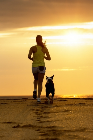Woman and dog running toward the sun on summer beach in a beautiful golden sunset  Sport girl and her pet training together