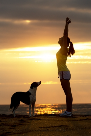Successful happy woman with her dog raising arms celebrating victory on beautiful golden summer sunset in the beach