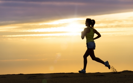Woman running alone on beautiful sunset in the beach Summer sport and freedom concept Athlete training on dusk