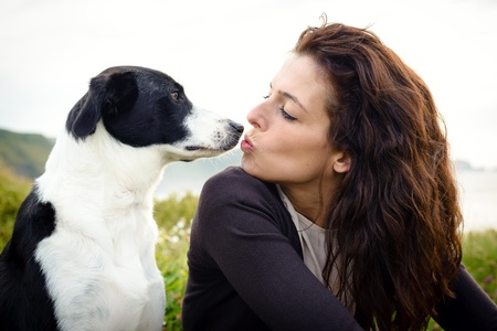 Dog and woman cute kiss and friendship  Woman with her pet on travel to coast  Stock Photo