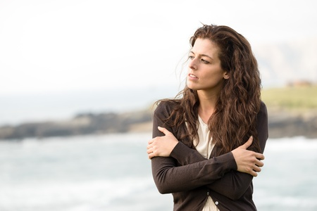 late summer: Sad shivery woman in brown sweater jacket hugging herself on late summer cold day in coast landscape. Sadness, melancholia and heart broken concept.