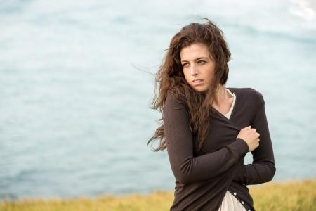 frio: Mujer temblorosa triste en la chaqueta su�ter marr�n abraz�ndose en fr�o de finales de verano y d�a de viento en el fondo del mar. La tristeza, la melancol�a y el concepto roto coraz�n.