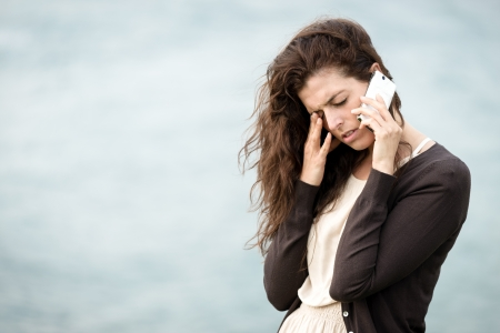 heartbreak issues: Sad worried woman receiving bad news by cellphone and crying. Trouble while on travel. Stock Photo