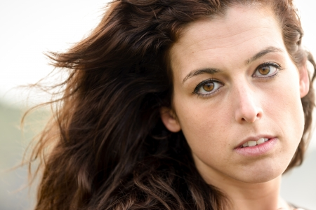 Natural close up portrait of sad woman. Serious girl face expressing sadness and nostalgia looking at camera. Stock Photo