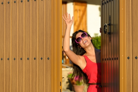 Happy woman opening her country house door to welcome guests visitors. Charming caucasian brunette girl good bye standing in home entrance. photo