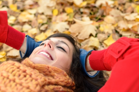 Happy woman on autumn season relax. Brunette girl lying down and smiling on fall golden leaves in park. Tranquility and peace concept. photo