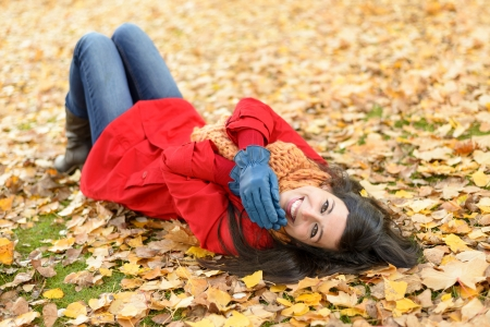 Woman lying down on autumn golden leaves and smiling. Positive happy brunette in red coat  enjoying on fall season. Caucasian girl looking at camera. photo