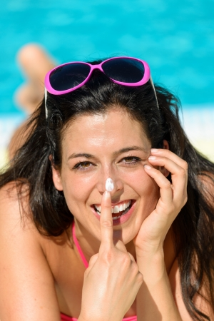 woman face cream: Funny woman sunbathing on summer at swimming pool. Woman enjoying sun with suntan lotion for skin solar protection. Happy playful girl on vacation joking. Stock Photo