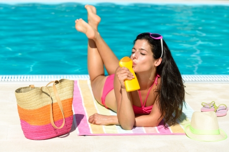 swimming pool woman: Funny woman sunbathing on summer at swimming pool. Woman enjoying sun with suntan lotion for skin solar protection. Happy playful girl on vacation joking and kissing sunscreen bottle. Stock Photo