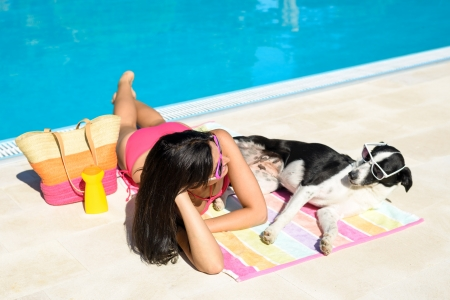 Woman and dog sunbathing together on funny summer at swimming pool like if they were talking to each other  Beautiful girl and her pet wearing sunglasses and having fun on holidays at poolside  photo