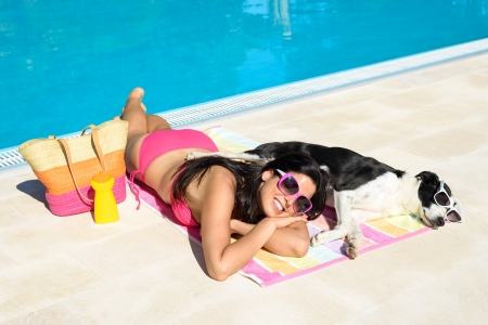 Woman and dog relaxing and sunbathing together on funny summer at swimming pool  Beautiful girl and her pet wearing sunglasses and having fun on holidays at poolside