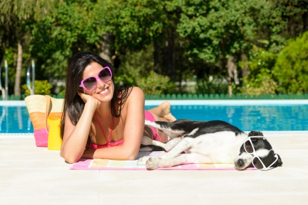 Woman and dog sunbathing and relaxing together on funny summer at swimming pool  Beautiful girl and her pet wearing sunglasses and having fun on holidays at poolside