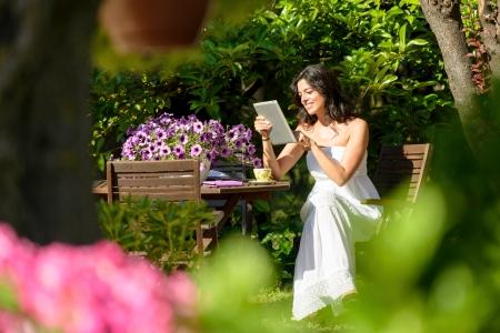 breakfast garden: Happy woman reading on tablet pc in garden on summer morning while breakfast. Woman enjoying communication technology on holidays. Stock Photo