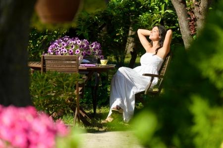 Gelukkig vrouw rust in de tuin op de zomer zonnige ochtend, omringd door bloemen en bomen. Jonge blanke brunette ontspannen en genieten van de buitenlucht.