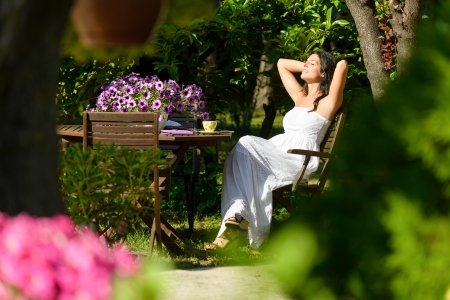 Happy woman resting in garden on summer sunny morning surrounded by flowers and trees. Young caucasian brunette relaxing and enjoying outdoors. Stock Photo