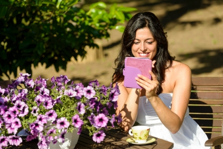 novel: Woman reading novel on ebook and enjoying morning breakfast on summer in garden. Female reader and electronic book. Stock Photo