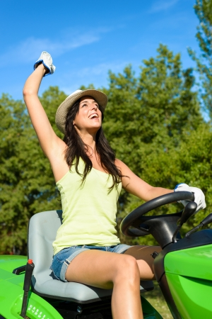 lawn mowing: Successful and happy female gardener riding garden tractor and raising arm. Woman riding lawn mower. Girl working on summer job.