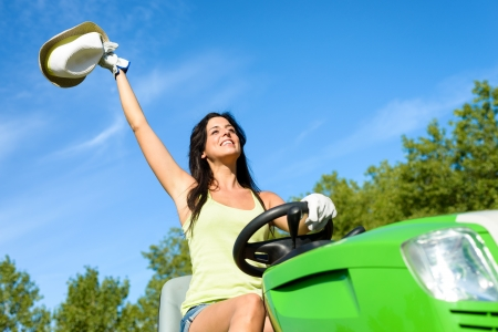 Successful woman riding green garden tractor. Happy female gardener driving and working with lawn mower for summer job. Stock Photo