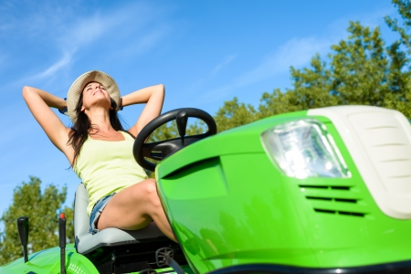 tondeuse: Jardinier Femme de d�tente et de repos apr�s tonte de la pelouse en �t�. Relaxed femme heureuse de prendre une pause apr�s avoir travaill� avec un tracteur de jardin.
