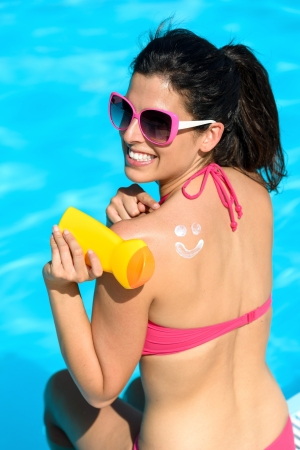 Funny woman applying sunscreen or suntan lotion on her back and sitting at poolside on summer holidays. Skin care and protection concept with cream drawing of smilie icon.