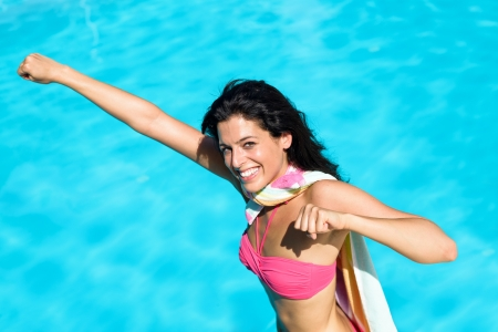 superheroine: Playful woman playing around in swimming pool on summer vacation. Happy super girl having fun ready to jump to the water in superwoman  superman pose like flying.