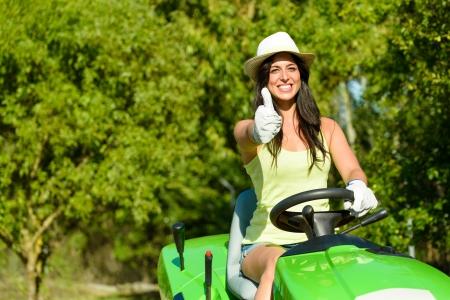 Succesvol en gelukkig vrouwelijke gardener riding tuin tractor doet goedkeuring gebaar met duim omhoog. Vrouw, paardrijden grasmaaier. Meisje dat aan vakantiejob.