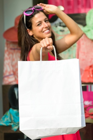 Woman holding blank shopping bags after buying clothes in sales  Successful and happy shopper  photo