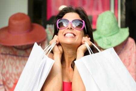 compras compulsivas: Mujer feliz después de hacer compras con sus bolsas blancas Comprador femenino muy emocionada y nerviosa después de comprar en las rebajas