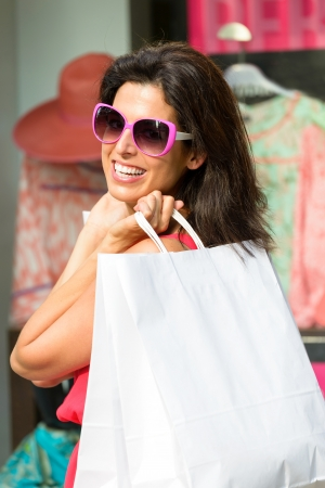 Woman holding white shopping bags and enjoying the commercial store sales  Happy caucasian fashion brunette after buying clothes  photo