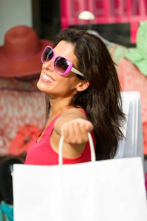 Blissful woman holding white shopping bags and enjoying the commercial store sales  Happy caucasian fashion brunette after buying clothes  photo